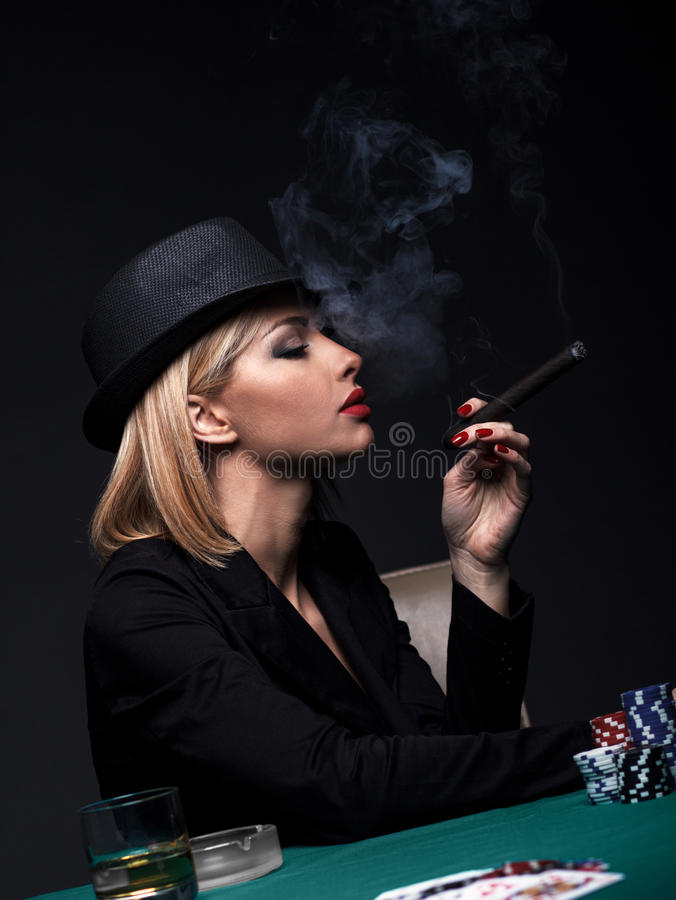 Beautiful young woman smokes a cigar during a poker game.  royalty free stock photography