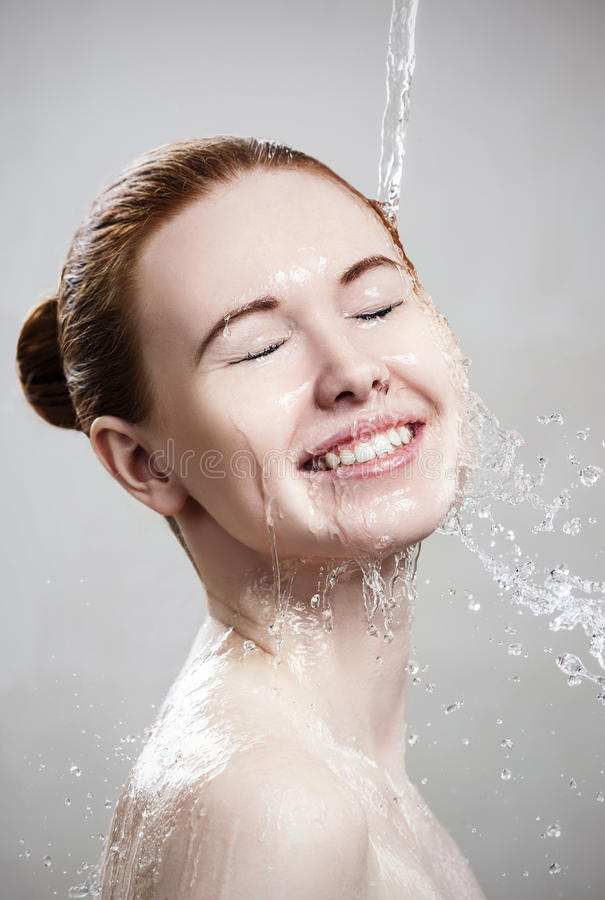 Beautiful young woman in splashes of clear water. stock image