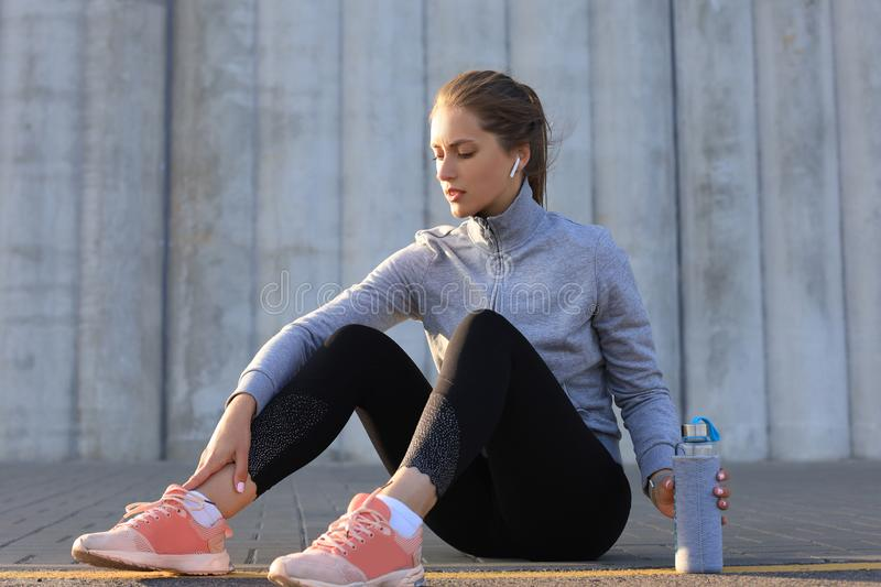 Beautiful young woman in sports clothing drinking water after sport exercise outdoors stock images