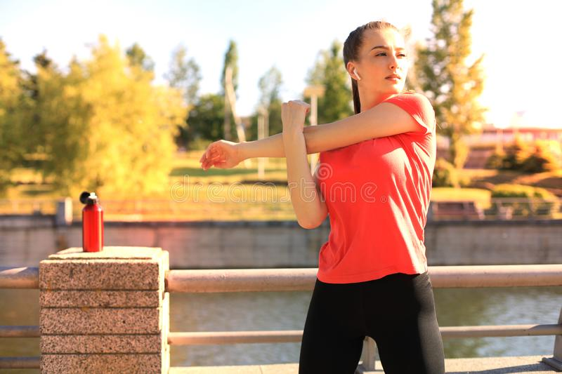 Beautiful young woman in sports clothing stretching her arms and looking concentrated while standing on the bridge stock image