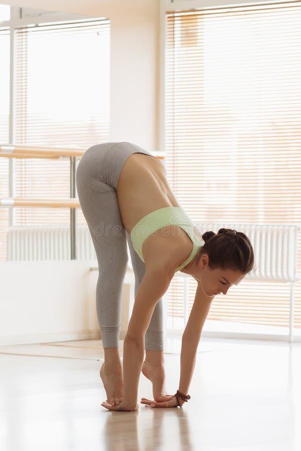 Beautiful young woman in sportswear lying in cobra pose while doing yoga in light studio stock photography