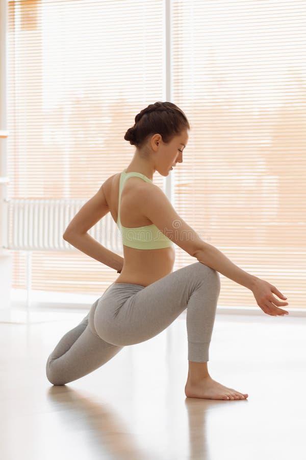 Beautiful young woman in sportswear lying in cobra pose while doing yoga in light studio stock image