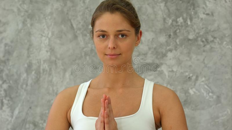 Beautiful young woman in sportswear practicing yoga and looking at camera while sitting in lotus position with namaste. Gesture. Close up. Professional shot in stock image
