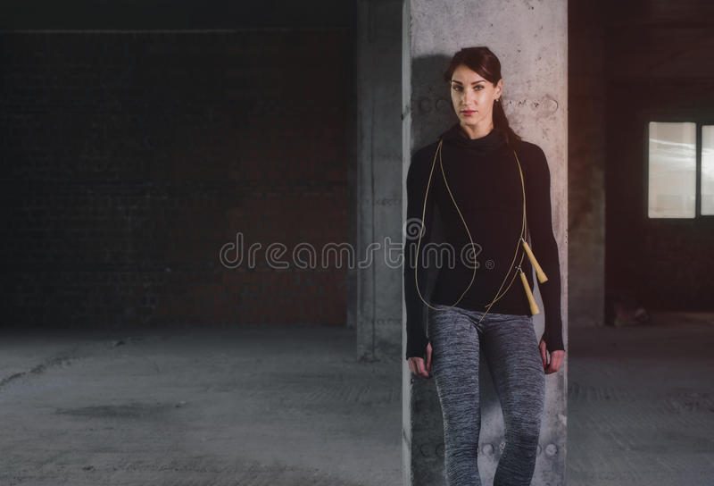 Young woman in sportswear standing near concrete column with jump-rope stock photos