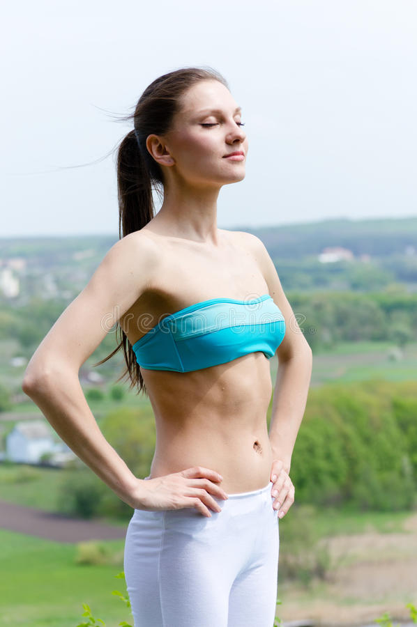 Beautiful young woman in sportwear outdoors on summer day stock photo