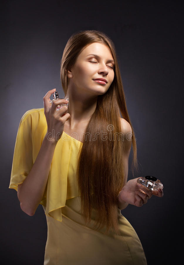 Beautiful young woman spraying perfume stock photography