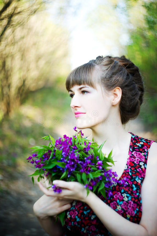 Beautiful young woman with spring flowers stock photography