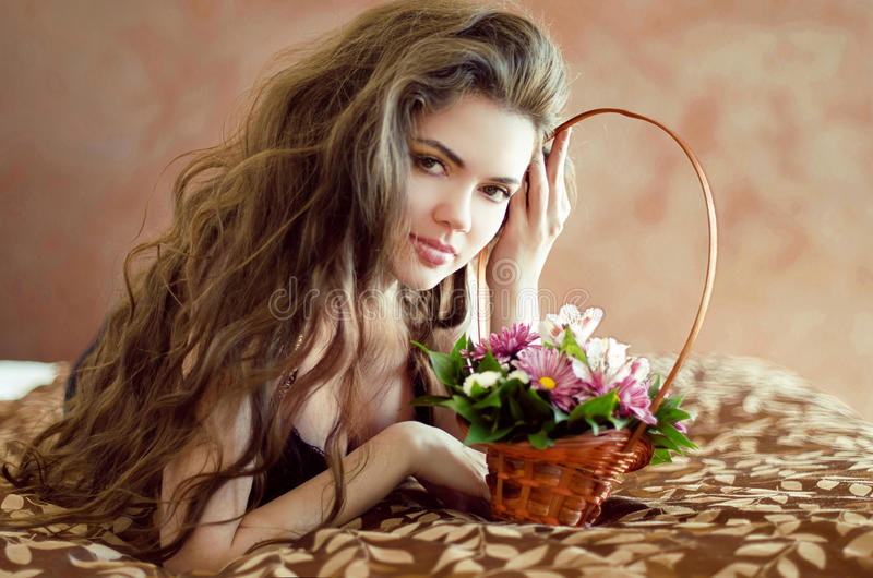 Beautiful young woman with spring flowers and long wavy hair lying on bedroom, beauty portrait, interior royalty free stock image