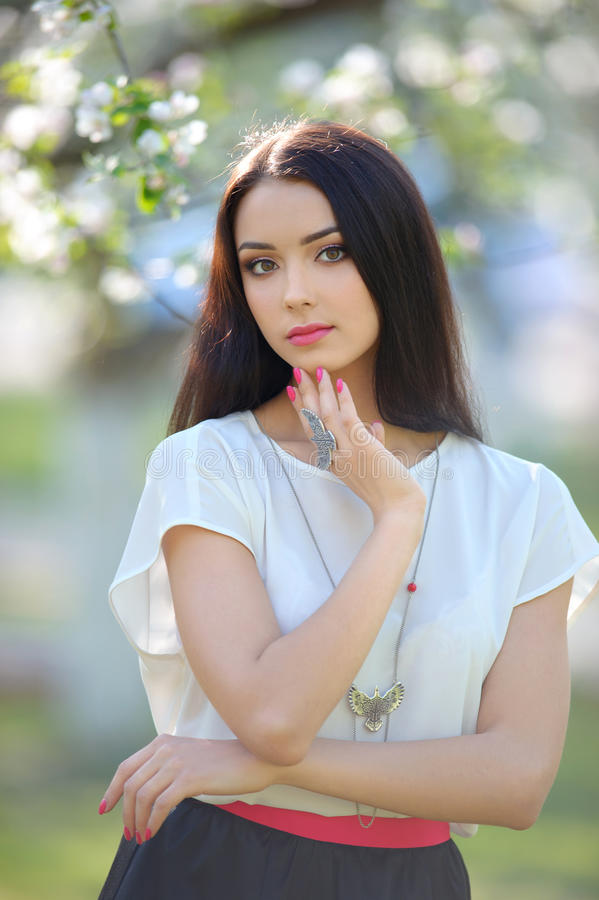 Beautiful young woman at the spring garden with stylish accessory collection. The Beautiful young woman at the spring garden with stylish accessory collection royalty free stock images