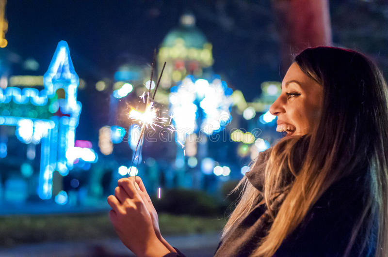 Beautiful young woman standing and holding sparklers over shining background. Woman holding sparkler in her hand, celebrating New Year`s Eve royalty free stock images