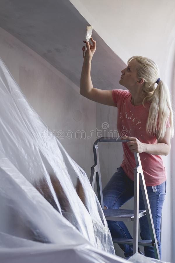 Painting a room by yourself. Housework activity. Renovating home. Beautiful young woman standing on ladder doing wall painting. Renovating and painting tips stock images