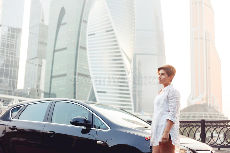 Beautiful young woman standing near black car on skyscrapers background stock photos