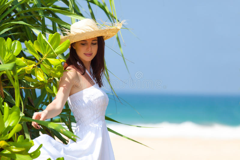 Beautiful young woman standing near exotic tree and smiling on t royalty free stock photography