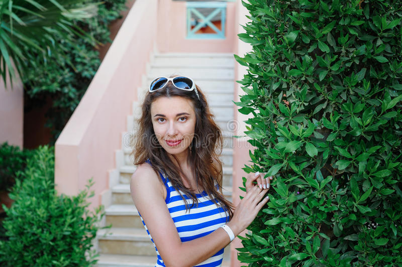 Beautiful young woman standing near a green bush in a park.  royalty free stock photo