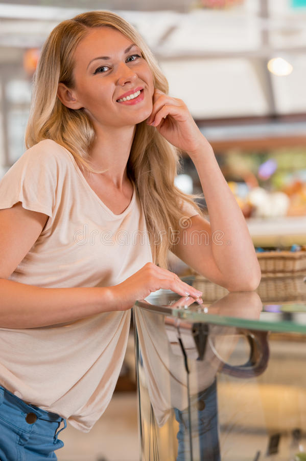 Beautiful young woman standing near supermarket showcase royalty free stock images