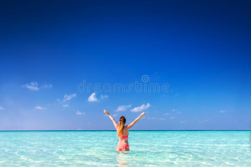 Beautiful young woman standing in the ocean with hands raised. Maldives royalty free stock images