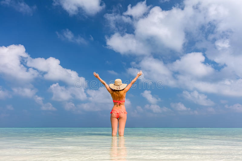 Beautiful young woman standing in the ocean with hands raised. Maldives stock photo