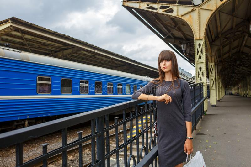 Beautiful young woman standing on the platform of railway station travel concept.  royalty free stock photography