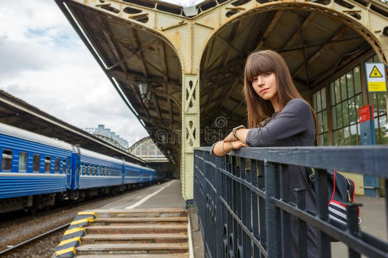 Beautiful young woman standing on the platform of railway station travel concept.  stock photo