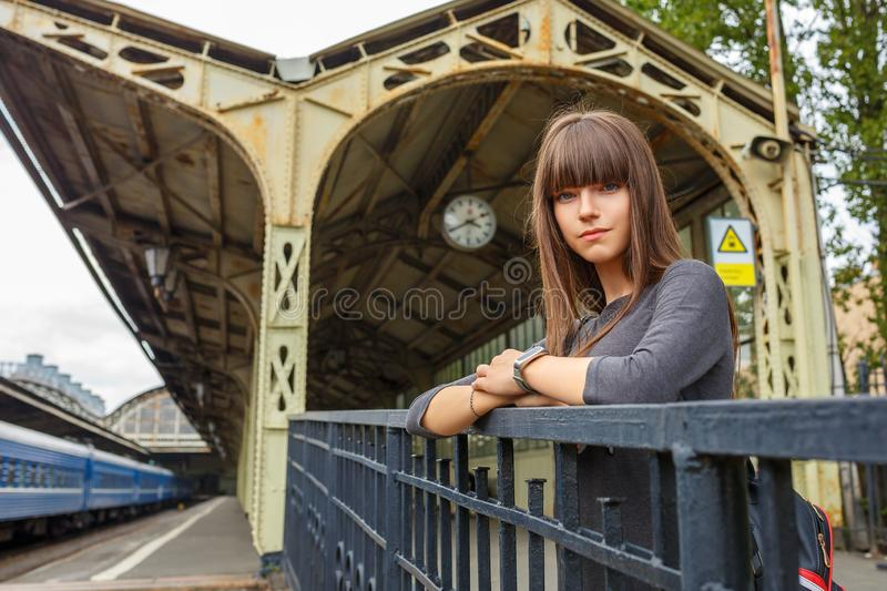 Beautiful young woman standing on the platform of railway station travel concept.  stock photography