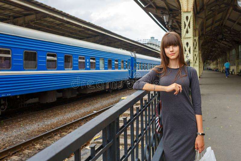 Beautiful young woman standing on the platform of railway station travel concept.  royalty free stock photo