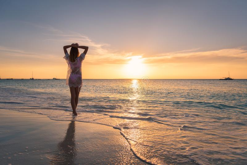 Beautiful young woman on the sandy beach at sunset stock photo