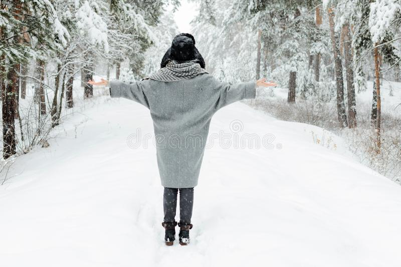Beautiful young woman standing among snowy trees in winter forest and enjoying snow. stock image