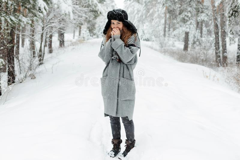 Beautiful young woman standing among snowy trees in winter forest and enjoying snow. stock photo