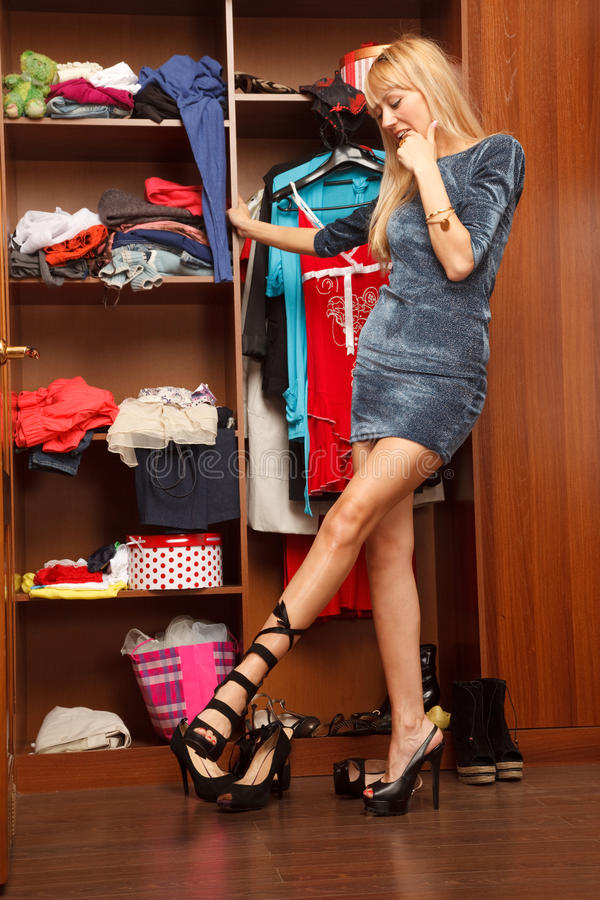 Beautiful young woman stands near her wardrobe in different sho stock photos