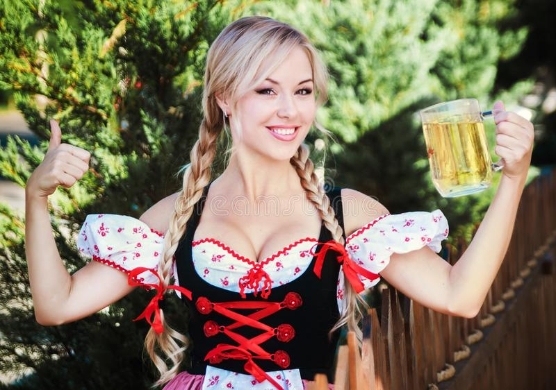 Beautiful woman in Octoberfest dress. Beautiful young woman on stone background in Octoberfest dress stock photos