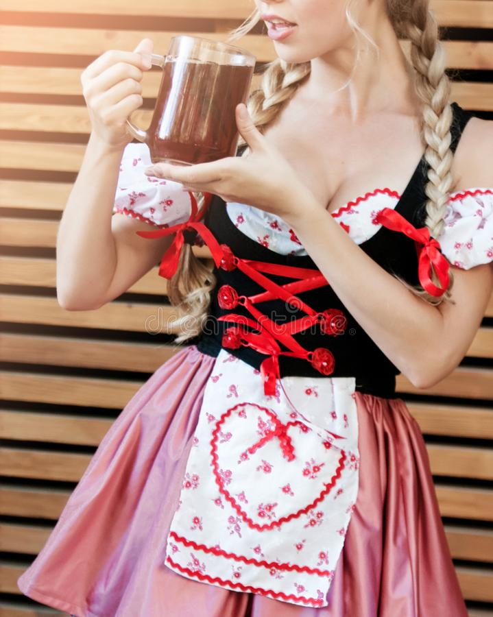 Beautiful woman in Octoberfest dress. Beautiful young woman on stone background in Octoberfest dress royalty free stock images