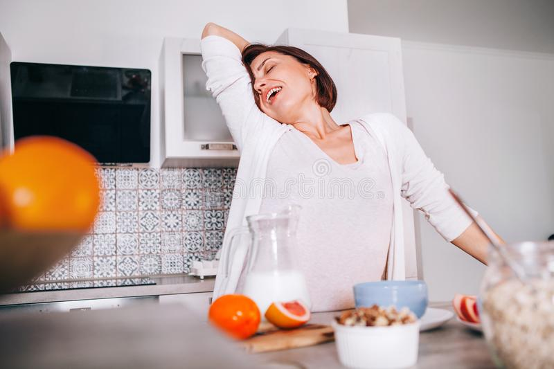 Beautiful young woman stretching after awakening and yawning at modern kitchen. New day beginning concept image royalty free stock photo