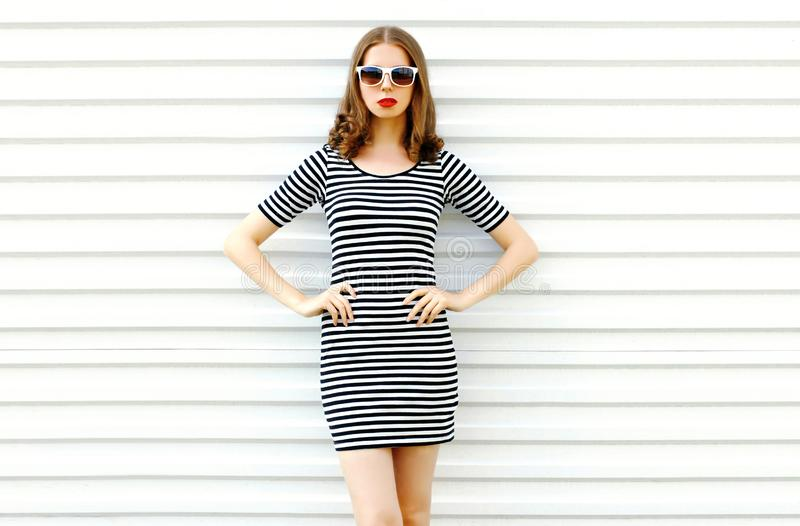 Beautiful young woman in striped dress posing on white wall stock images