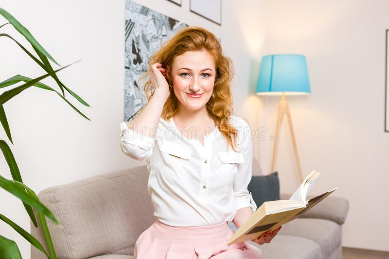 Beautiful young woman student with long red hair in pink skirt and shirt reading book,holding in hand textbook sitting on sofa hom royalty free stock images