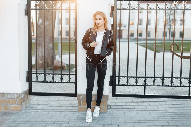 Beautiful young woman in a stylish black jacket in a white polo shirt in fashionable jeans in white sneakers stands. Near the metal vintage gates against the stock image