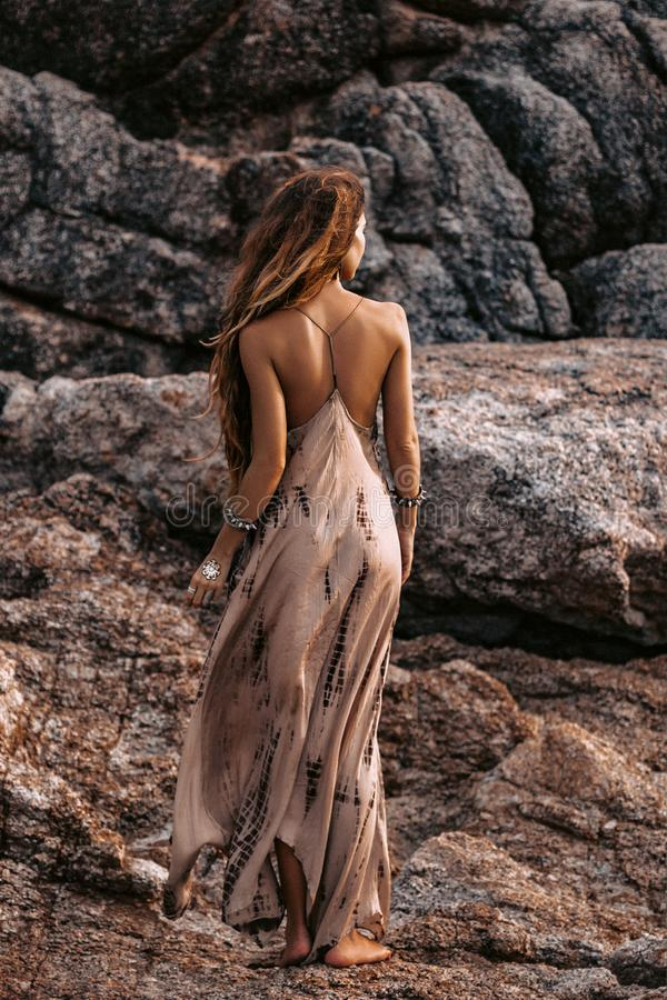 Beautiful young woman in stylish boho dress posing outdoors at sunset royalty free stock images