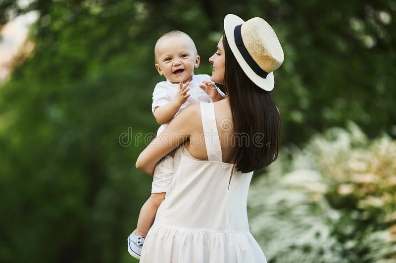 Beautiful young woman in the stylish hat and in a white dress with her cute little son in shirt and shorts on her hands stock photo