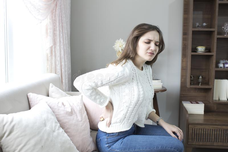 Beautiful young woman suffering from backache at home. royalty free stock photos
