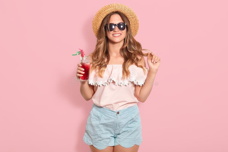 Beautiful young woman in summer blouse, blue short , black sunglasses and straw hat holding glass with cold beverage while stock photos