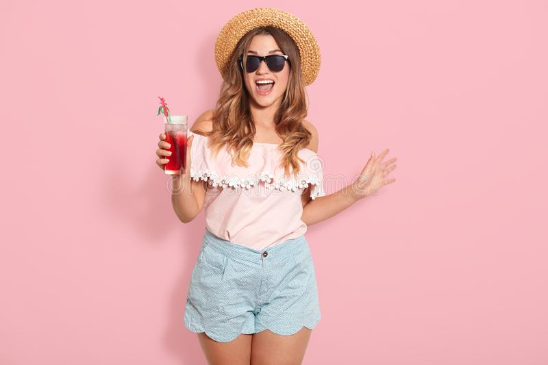 Beautiful young woman in summer blouse, short, hat and sunglasses, holding jug with cold beverage while standing on pink. Background, enjoing of spending her royalty free stock photography