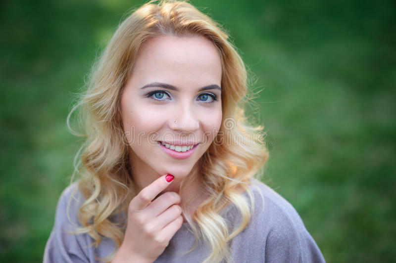 A beautiful young woman in the summer Park poses royalty free stock photos