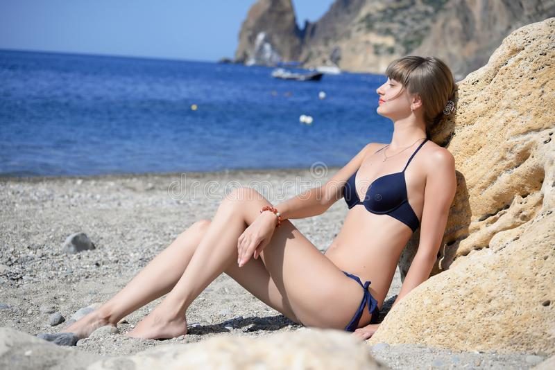 Beautiful young woman sunbathes on the beach stock images