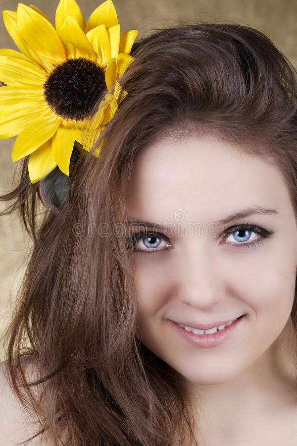 Beautiful young woman with a sunflower royalty free stock image