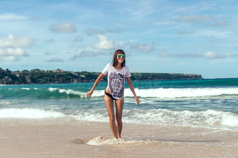 Beautiful young woman in sunglasses posing on the beach of a tropical island of Bali, Indonesia. stock photography