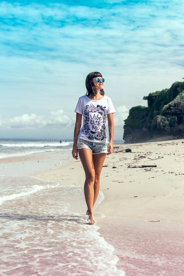 Beautiful young woman in sunglasses posing on the beach of a tropical island of Bali, Indonesia. stock photo