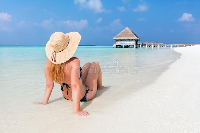 Beautiful young woman in sunhat sitting relaxed on tropical beach in Maldives royalty free stock photos