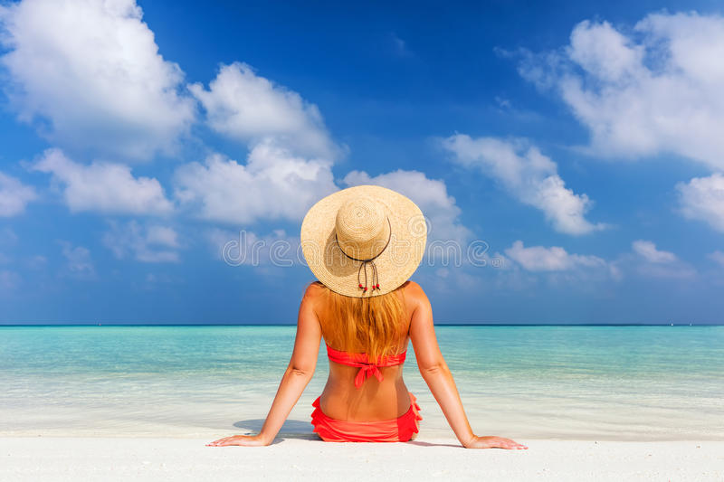 Beautiful young woman in sunhat sitting relaxed on tropical beach in Maldives stock photos