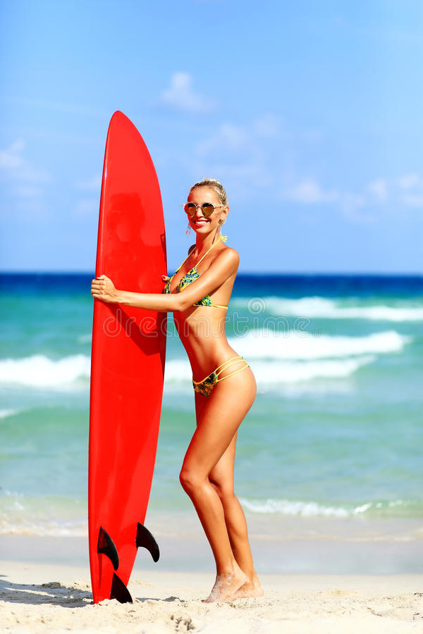 Beautiful young woman surfer girl in bikini with red surfboard a stock photos