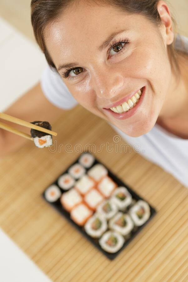Beautiful young woman with sushi roll royalty free stock photos