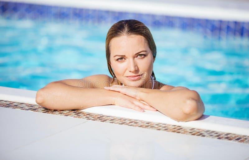 Beautiful young woman in swimming pool stock photo